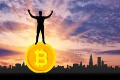 Homem feliz que está em um bitcoin da moeda Fotografia de Stock Royalty Free