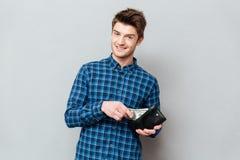 Homem feliz que está sobre a parede cinzenta que guarda a bolsa com dinheiro Fotos de Stock Royalty Free