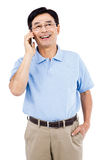 Homem feliz que fala no telefone celular ao estar Imagens de Stock Royalty Free