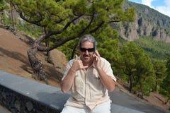 Homem feliz que fala pelo telefone no banco no parque Fotos de Stock Royalty Free
