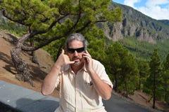 Homem feliz que fala pelo telefone no banco no parque Foto de Stock