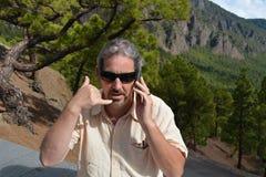 Homem feliz que fala pelo telefone no banco no parque Imagens de Stock