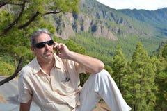 Homem feliz que fala pelo telefone no banco no parque Imagem de Stock Royalty Free