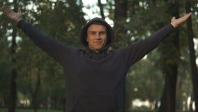 Homem feliz que faz exercícios de respiração na harmonia do parque, do corpo e da mente, esporte filme