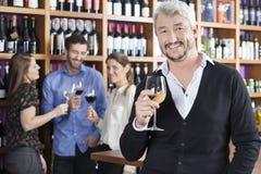 Homem feliz que guarda o copo de vinho com os amigos no fundo fotografia de stock
