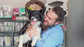 Homem feliz que guarda seu cão adorável, sorrindo à câmera filme