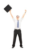 Homem feliz que guarda uma mala de viagem e que gesticula a felicidade com aumento Fotos de Stock Royalty Free