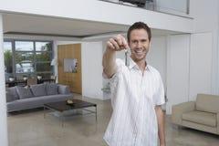 Homem feliz que guardara chave na casa nova Fotografia de Stock Royalty Free