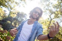 Homem feliz que joga Air Guitar no parque Fotografia de Stock Royalty Free