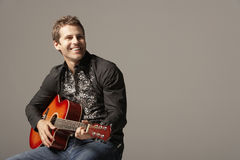 Homem feliz que joga a guitarra Imagens de Stock
