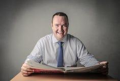 Homem feliz que lê o jornal Foto de Stock Royalty Free