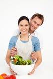 Homem feliz que mistura uma salada com sua amiga imagens de stock royalty free