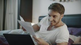 Homem feliz que olha papéis de negócio em casa Homem de negócios bem sucedido que acena sim video estoque