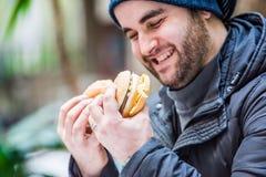 Homem feliz que olha um hamburguer e um sanduíche - ascendente próximo Imagem de Stock Royalty Free