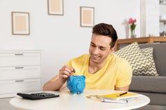 Homem feliz que põe a moeda no mealheiro na tabela Dinheiro da economia imagem de stock
