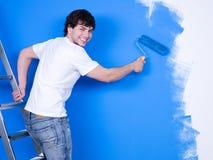 Homem feliz que pinta a parede imagem de stock