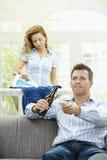 Homem feliz que presta atenção à tevê Imagem de Stock