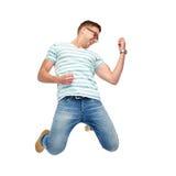 Homem feliz que salta e que joga a guitarra imaginária Imagem de Stock Royalty Free