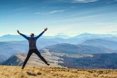 Homem feliz que salta na parte superior da montanha foto de stock royalty free