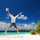 Homem feliz que salta na praia tropical Fotos de Stock