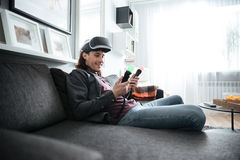 Homem feliz que senta em casa dentro jogos do jogo Fotos de Stock