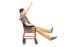 Homem feliz que senta-se em uma cadeira de rodas e em gesticular Fotos de Stock