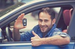 Homem feliz que senta-se no carro novo que mostra os polegares das chaves acima imagem de stock royalty free