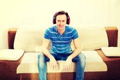 Homem feliz que senta-se no sofá e na música de escuta fotografia de stock
