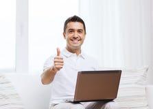 Homem feliz que trabalha com laptop em casa Fotos de Stock Royalty Free