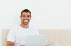 Homem feliz que trabalha em seu portátil em seu quarto imagens de stock