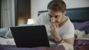 Homem feliz que usa o computador port?til em casa Homem de sorriso que conversa em linha no caderno filme