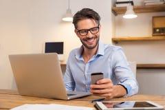 Homem feliz que usa o smartphone fotos de stock
