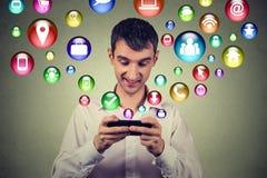 Homem feliz que usa texting nos ícones sociais da aplicação dos meios do smartphone que voam acima Fotografia de Stock Royalty Free