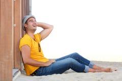 Homem feliz relaxado que senta-se na areia na praia com chapéu imagens de stock
