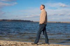 Homem feliz, vestindo ocasionalmente, andando ao longo da praia, na mágica a Fotos de Stock