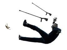 Homem ferido com as muletas que deslizam a silhueta Imagens de Stock