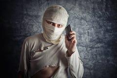 Homem ferido com ataduras principais usando o telefone celular Foto de Stock Royalty Free