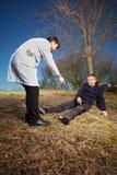 Homem ferido de ajuda do paramédico retro do estilo no parque da cidade Imagem de Stock Royalty Free