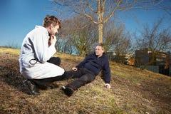 Homem ferido de ajuda do paramédico retro do estilo no parque da cidade Fotos de Stock
