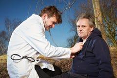Homem ferido de exame do paramédico retro do estilo no parque da cidade Imagem de Stock