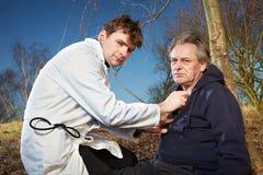Homem ferido de exame do paramédico retro do estilo no parque da cidade Foto de Stock Royalty Free