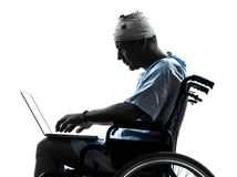Homem ferido na silhueta de computação do computador portátil da cadeira de rodas Fotografia de Stock Royalty Free