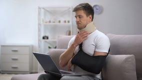 Homem ferido no colar cervical da espuma e no estilingue do braço que trabalham na dor de sentimento do portátil vídeos de arquivo