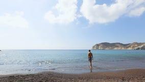 Homem fino em banhar o short que tenta a água antes de mergulhar no Mar Egeu infinito filme
