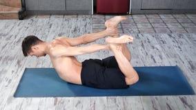 Homem flexível da aptidão que aprecia os pilates que fazem o esticão do encontro no ângulo alto da esteira video estoque