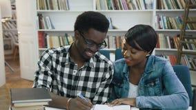 Homem focalizado do africano e estudantes fêmeas que preparam-se aos exames na biblioteca vídeos de arquivo