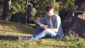 Homem focalizado que senta-se na grama e no livro de leitura filme