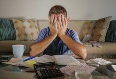 Homem forçado preocupado atrativo em casa que calcula despesas do imposto do mês com os pagamentos da contabilidade da calculador imagens de stock royalty free