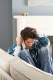 Homem forçado que senta-se no sofá em casa no telefone Imagens de Stock Royalty Free