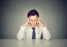 Homem forçado triste sério que senta-se no pensamento da tabela imagem de stock